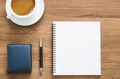 Table en bois de bureau avec le carnet, le stylo, le portefeuille et la tasse vides de Co Images libres de droits