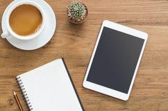 Table en bois de bureau avec le comprimé, le carnet, le crayon et la tasse de coffe Image libre de droits