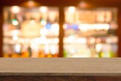Table en bois de perspective sur le dessus au-dessus de la vinothèque de tache floue dans le dos de café Photographie stock libre de droits
