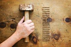 Table en bois de vintage avec le marteau et les clous Image libre de droits
