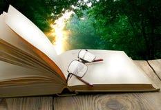 Table en bois en verre ouverts de livre sur un fond Photographie stock libre de droits