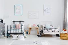 Table en bois entre le lit noir et blanc chez la chambre à coucher international des enfants photographie stock