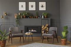 Table en bois entre les fauteuils gris dans le rétro intérieur plat avec photographie stock
