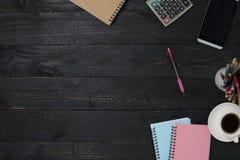 table en bois noire de bureau avec le smartphone, les fournitures de bureau et le coffe Photographie stock libre de droits