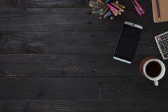 table en bois noire de bureau avec le smartphone, les fournitures de bureau et le coffe Photo libre de droits