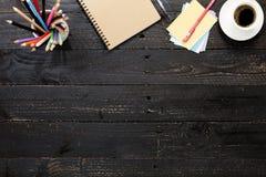 table en bois noire de bureau avec le smartphone, les fournitures de bureau et le coffe Images libres de droits