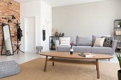 Table en bois ronde au milieu de salon élégant avec le sofa gris, d'étagère en métal et de miroir, vraie photo avec l'espace de c images libres de droits