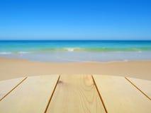 Table en bois sur la plage brouillée Image libre de droits