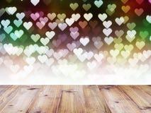 Table en bois sur le bokeh de coeur pour le fond de jour du ` s de Valentine Image stock