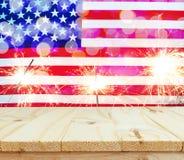 Table en bois sur le drapeau des Etats-Unis avec le fond de cierges magiques Image stock