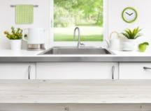 Table en bois sur le fond de fenêtre d'évier de cuisine Image stock