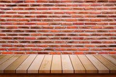 Table en bois vide avec le fond rouge de mur de briques Photos stock