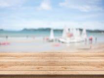 Table en bois vide dans l'avant avec le fond brouillé à la plage images libres de droits