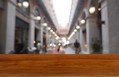 Table en bois vide devant le fond brouillé abstrait du centre commercial et des personnes Peut être employé pour l'affichage ou l photographie stock libre de droits