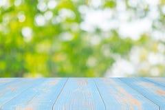 Table en bois vide sur le fond naturel vert dans le jardin extérieur Raillez pour votre affichage ou montage de produit images libres de droits