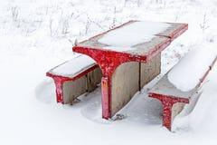 Table et chaises concrètes dans la neige Photo stock