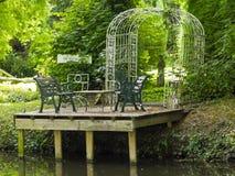 Table et chaises de pique-nique situées sur une rivière tranquille Images stock
