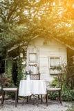 Table et présidences blanches dans le beau jardin Photos stock