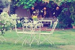 Table et présidences blanches dans le beau jardin Pictur de style de vintage Images libres de droits
