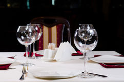 Table in Fancy Restaurant Set for Dinner. With Wine Glasses Stock Photo