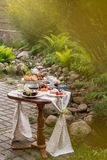 Table with festive treat and tablecloth in the summer garden stock photography