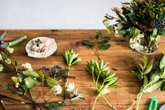 Table of florist. Florist workspace. Scissors, skein harness. Old wooden table. The working surface. Make a bouquet. Hobbies, business occupation Royalty Free Stock Photos
