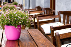 Table with flowers and chairs in street cafe Stock Photo