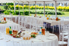 Table with food and drinks at outdoor banquet Stock Photos