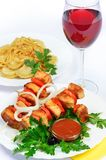 Table with food of meat on skewer, dumplings and gass of red win Royalty Free Stock Images