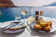 Table with food and wine on the sea. Table with food and wine on the background of the sea stock images