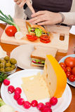 Table with food and woman halving sandwich Stock Photos