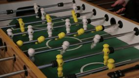 The Table Football Goal. Two men playing table football yellow and white players foosball stock footage