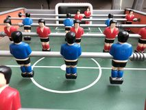 Table Football. Player figures on table football - red & blue teams but lost ball , fusball Stock Photo