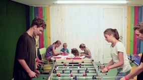 Table football playing, two teams of teens playing board games indoor, children playing table soccer stock footage