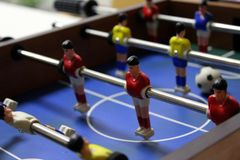 Table football soccer game kicker. sports team players in red and yellow t-shirts stock photos