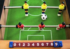 Table football soccer with a scoreboard. Yellow and red players on a vivid green field with a big ball. Two metal rods and wooden sides. Table game for sport Royalty Free Stock Photos