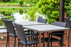 Table with four chairs beside the beautiful river Royalty Free Stock Image