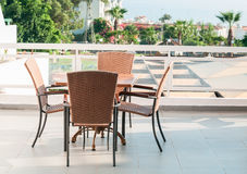 Table with four chairs standing on open air terrace Stock Photos