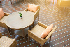 Table with four chairs in the sun on wooden floor Royalty Free Stock Image