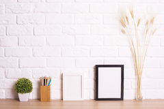 Table with frames. Wooden table with decorative blank picture frames, plant, wheat spikes and stationery items on white brick wall background. Mock up Royalty Free Stock Photos