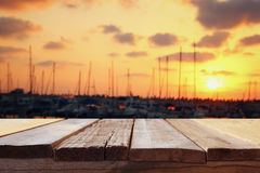 Table in front of abstract blurred yachts at sunset. Image of wooden table in front of abstract blurred yachts in pier at sunset Royalty Free Stock Photography