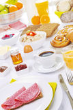 Table full with continental breakfast items, brightly lit Royalty Free Stock Photography
