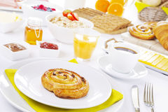 Table full with continental breakfast items, brightly lit Royalty Free Stock Image