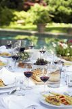 Table full of food and wine in backyard Stock Images