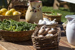 Table full of fresh garden variety vegetables. Wood table with baskets of colorful home grown fresh garden variety fruits and vegetables Stock Images