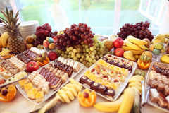 Table full of fruits and small cakes Stock Images