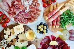 Table full of mediterranean appetizers. Tapas or antipasto. Assorted Italian food set. Delicious snack on party or picnic time. Chopping board with meat and royalty free stock images