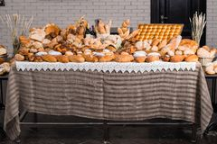 Table full of various types of fresh bread. Wheat and rye breads. Challah, rum baba, French baguettes and others stock image