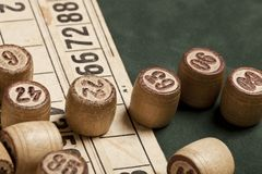 Table game Bingo. Wooden Lotto barrels with bag, playing cards for Lotto games, games for family. stock photos