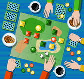 Table game flat  illustration. Family board game with player`s hands. Board game on table with map and playing cards, chips, dices. Table with coffee cups Stock Photography